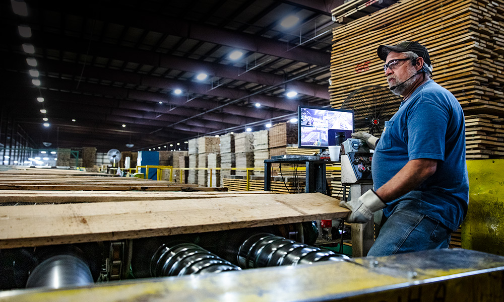 employee working with lumber near a control panel