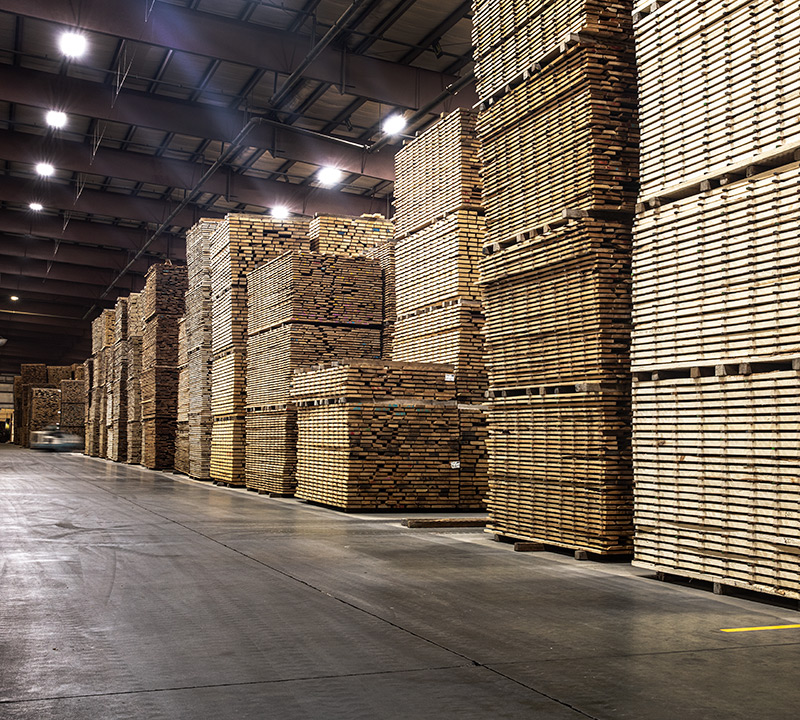 stacks of cut lumber standing in a Granite Valley Forest Products warehouse