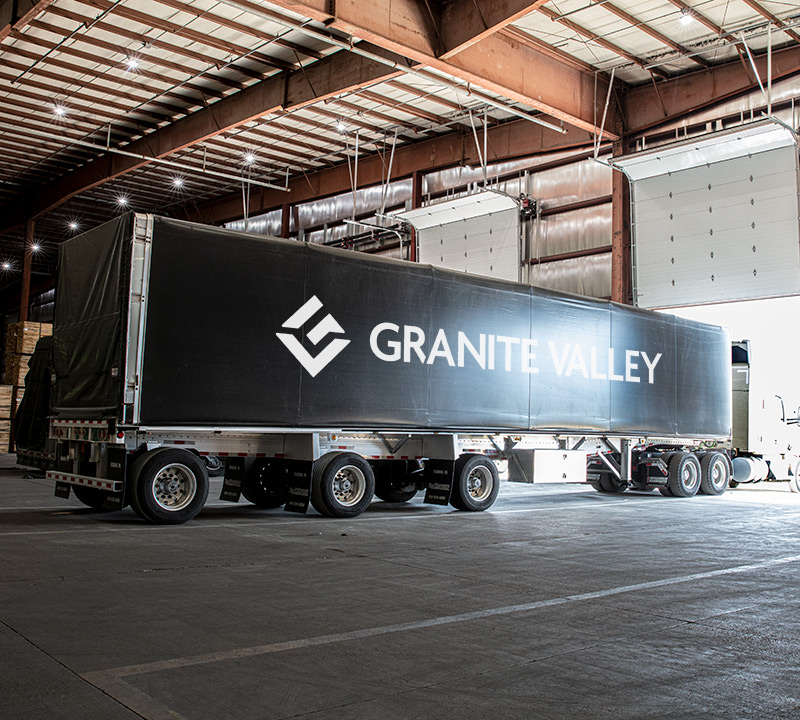 a semi trailer with a Granite Valley Forest Products logo parked inside of a Granite Valley Forest Products facility