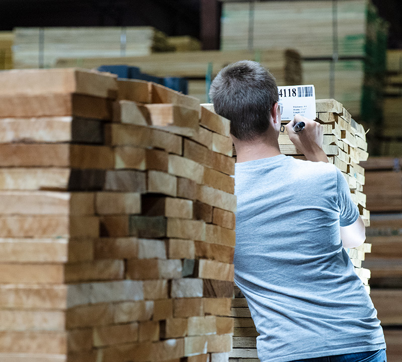 Granite Valley Forest Products employee seen from behind while marking lumber with a marker
